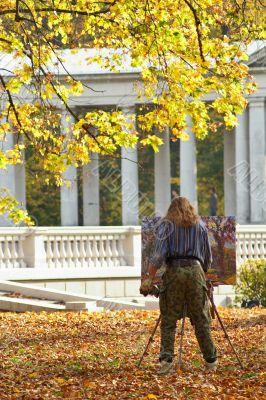 Painter in autumn park