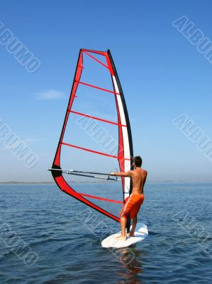 Windsurfer on waves of a gulf in the afternoon