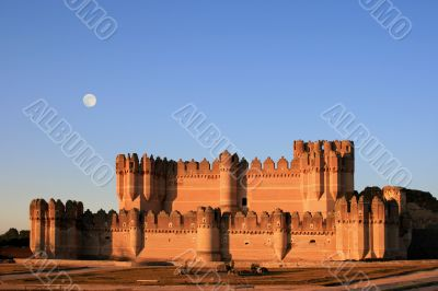 The fortress of Coca (Spain) at dusk with full moon