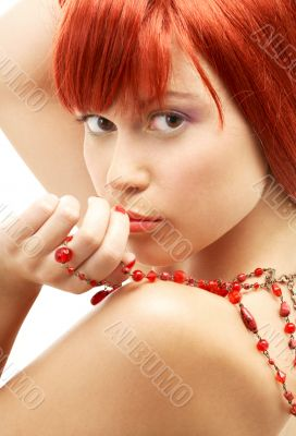 redhead with red beads looking over shoulder