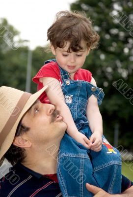 little girl is sitting on daddy`s shoulder