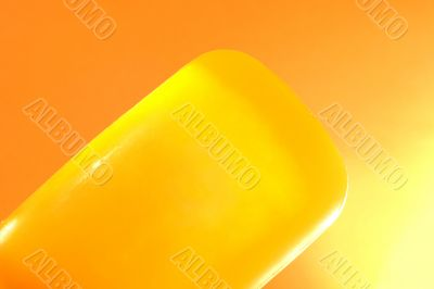 Piece of yellow soap on an orange background