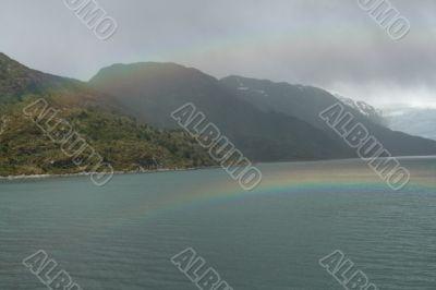 Rainbow, rocky hills and glacier