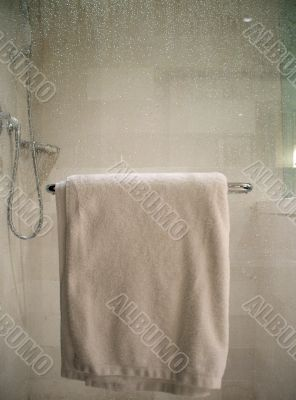 White Towel on Rack on Wet Glass Shower Door