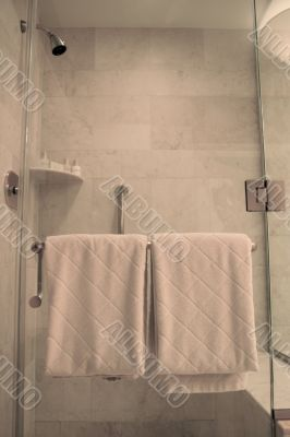 White Towels on Rack on Wet Glass Shower Door