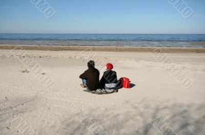 Woman and Man Sitting on Sand Watching Sea in Spring
