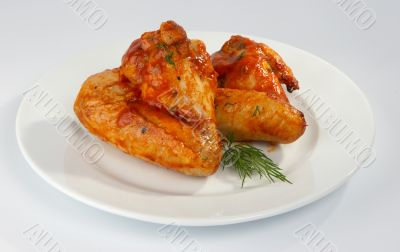 Fried chicken wings in tomato sauce.