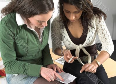 Two teenage girls checking pregnancy test