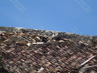 Roof tiles of an old, damaged villa