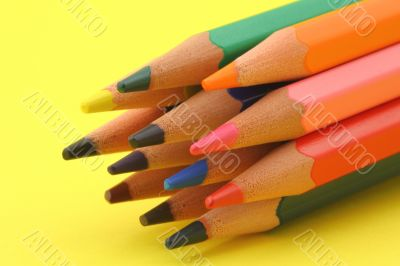 bunch of colorful pencils on yellow background