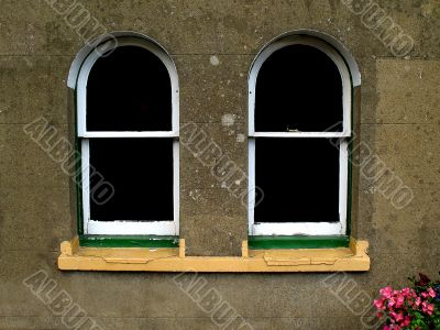 Two arched windows in textured stonework