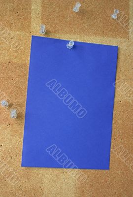 blue paper sheet pinned to corkboard