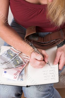 Woman writing down her expenses