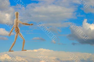 woden figure walking on clouds
