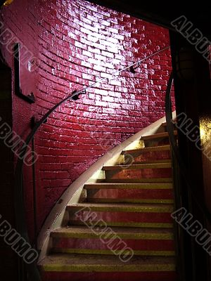 Spiral staircase and stark red brick wall