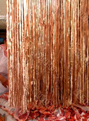 Butcher Behind A Curtain Of Fresh Meat