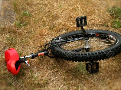 A unicycle with red seat at rest