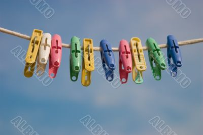 Clothespins on a cord on a background of the sky