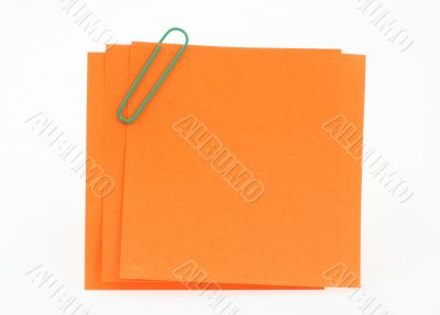three orange notes with green paperclip
