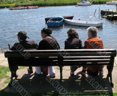 four friends relaxing at the waters edge