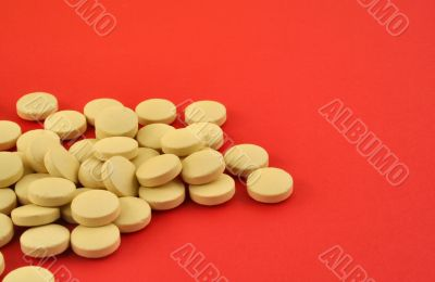 handful of yellow tablets on red
