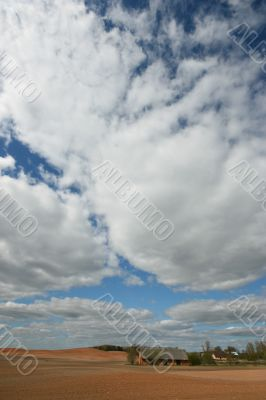 Country house in plough-land under cloudy sky in spring