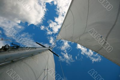 Mast with sails on sky background