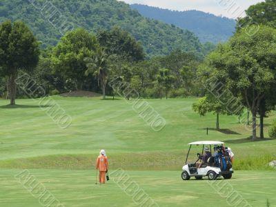 Caddie and golf cart on the fairway
