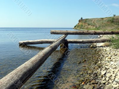Logs and stones on seacoast