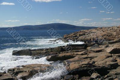 Breaking waves on granite ledges