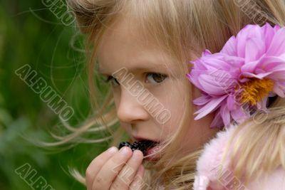 little girl eats blackberry