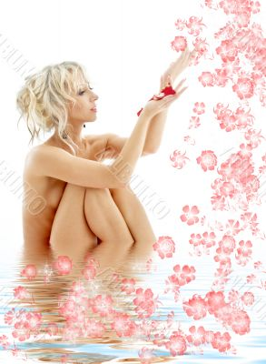naked blond with rose petals and flowers in water