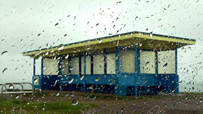 beach shelter seen through rain covered glass