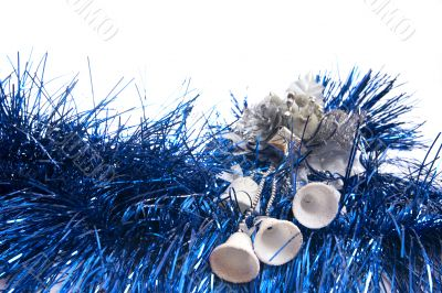 white bells lie on blue new-year tinsel