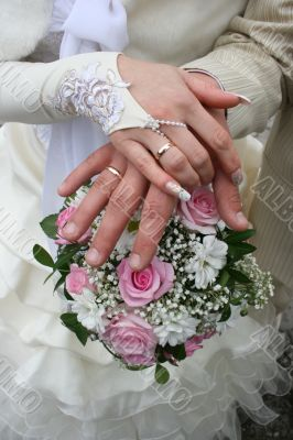 Female and male newlyweds hands with bouquete