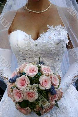 Bride torso with bouquet in white wedding dress