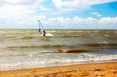 Windsurfing. Seashore. Hot sand. Dark blue sky.