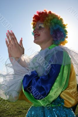 Expressive clown in colored wig upon blue sky