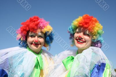 Two bizzare clowns in colored wigs upon blue sky