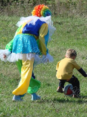 Clown in colored wig plays with child