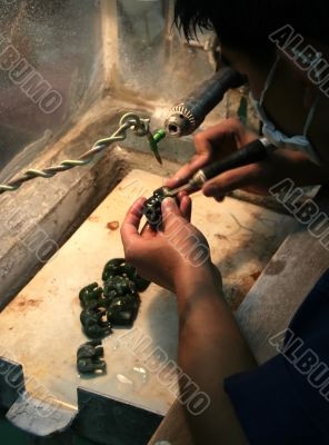 Asian man polishing a small jade elefants