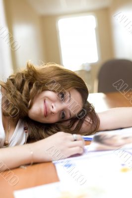Attractive girl relax on a table after reading fashion magazine