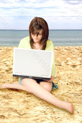 casual girl using a laptop on the beach