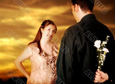 couple at sunset - guy hiding flowers from her