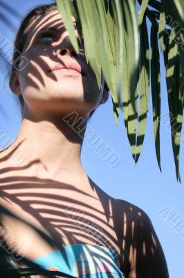 Beautiful woman in bikini with leafy shade