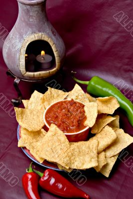 candle, chips, salsa and peppers on burgundy background