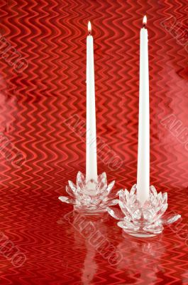 Two White Candles in Crystal Candleholders with Red Backgrounc