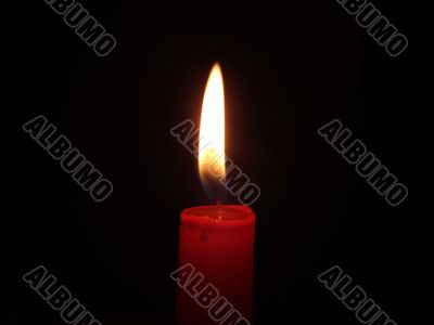 The red candle burning in full darkness