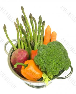 Fresh vegetables in a colander on white isolated