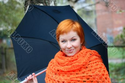 young red-haired woman in red scarf with umbrella